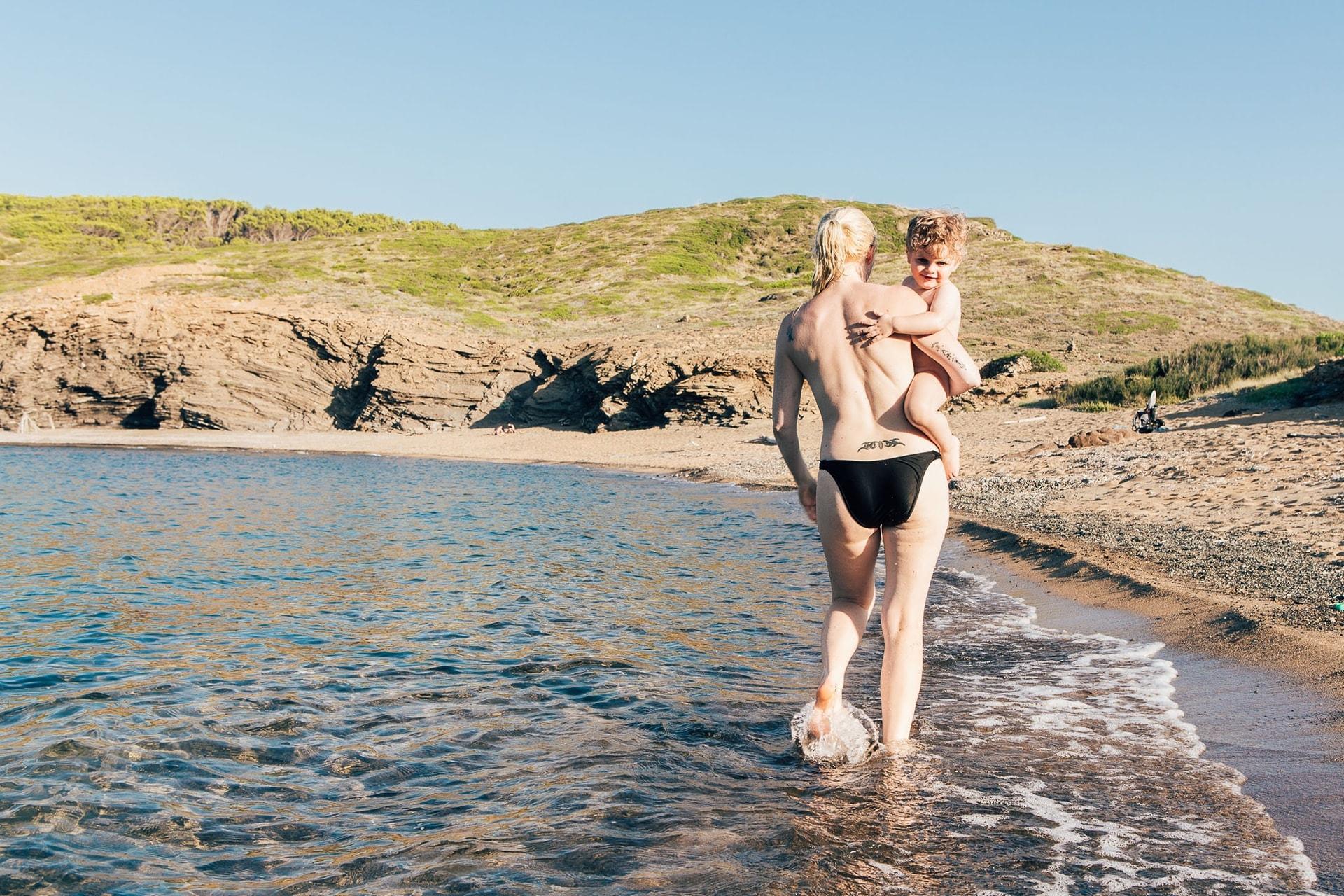 Sabine porte Soren au bord de l'eau à Cala Mica